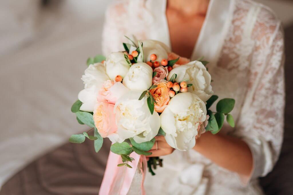 peonies roses ranunculus snowberries white orange bridal bouquet